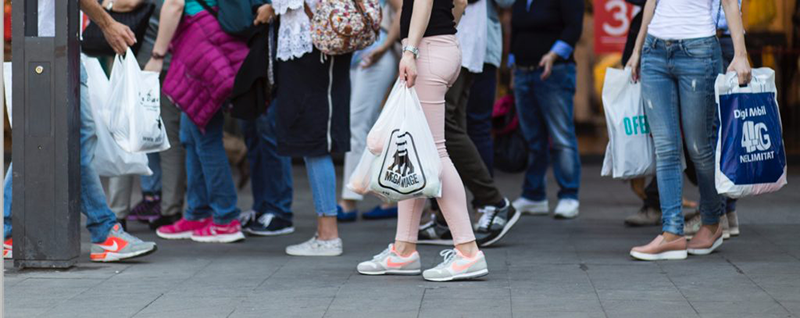 viandantes con bolsas de plástico por la calle